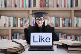 Female graduate thumbs up in library — Stock Photo
