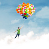 Woman flying with balloons — Stock Photo