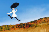 Young woman jumping with holding umbrella — Stock Photo