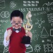 Cute nerd holding trophy in class — Stock Photo