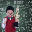Cute nerd holding trophy in class — Stockfoto