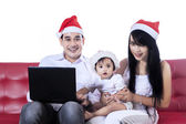 Christmas family playing with laptop — Stock Photo