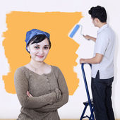 Asian couple painting wall in yellow — Stock Photo