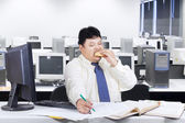 Fat businessman working while eating — Stock Photo
