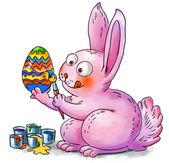 Easter bunny decorates eggs — Stock Photo