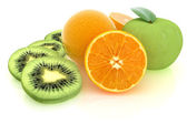 кусочки киви, яблоко, апельсин и половину апельсина на белом — Стоковое фото