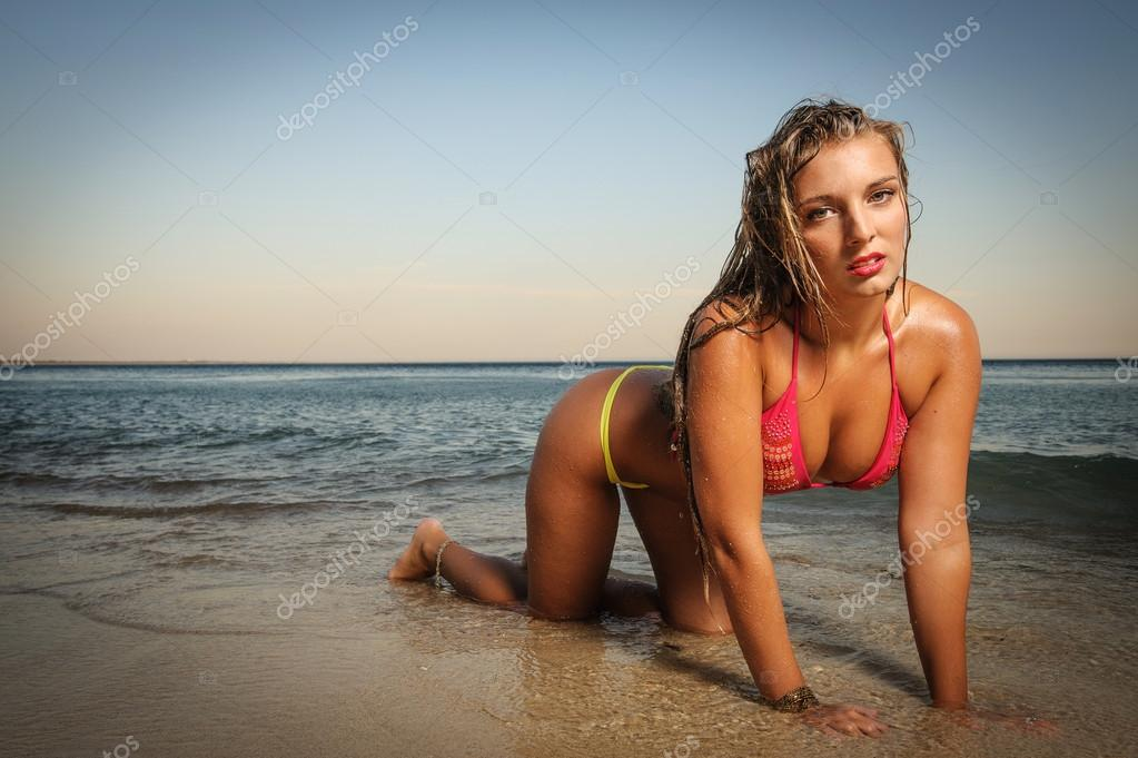 Sexy blond woman in bikini wet at the water line looking at the camera — Stock Photo #16173377