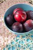 Ripe pulms in blue plate — Stock Photo