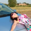 Sexy girl lying on the car — Stock Photo