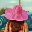 Long-haired woman standing near the car back — Stock Photo
