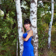 Happy girl in a long blue dress stands near the birch — Stock Photo