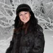 Beautiful girl stands near the snow-covered tree — ストック写真
