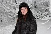 Bella ragazza si leva in piedi vicino all'albero innevato — Foto Stock