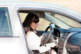 Young woman in a car ignition key inserts — Stock Photo