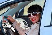 一个女孩在一辆车与信用卡和现金在手 — 图库照片