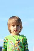 The little girl on a background of blue sky — Stock Photo