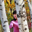 Beautiful girl looks out from behind a birch — Stock Photo