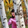 Beautiful girl looks out from behind a birch — Stock Photo #14831851