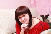 Kanepede oturan genç bir kadın — Stok fotoğraf