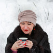 Girl in winter forest drinking tea from a cup — Stock Photo
