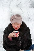 Beautiful girl holding a cup of tea in the winter forest — Stock Photo