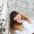 Young girl talking on the phone near the birch — Stock Photo #20347317