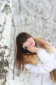 Young girl talking on the phone near the birch — Stock Photo