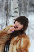 Young brunette eating candy in a winter forest — Stock Photo
