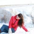 The girl in the fresh air, sitting on the white snow — Stock Photo