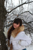 A young girl in a white jacket near a tree — Stock Photo