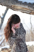 Girl in leopard dress talking on the phone — Stok fotoğraf