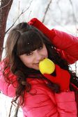 Young brunette in a winter forest, eating apple — Stock Photo