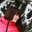 Happy girl near the snow-covered fir — Stock Photo