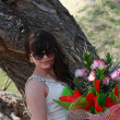 Girl in sunglasses with a bouquet of roses, near the old oak — Stock Photo