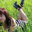 Stock Photo: A young woman lies on the grass