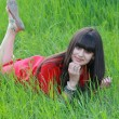 Stock Photo: The girl in the red dress is resting on green grass