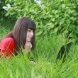 Stock Photo: Young brunette with a laptop in the grass