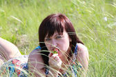 A young brunette woman eating a strawberry while lying in the gr — Stock Photo