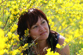 Thoughtful girl in the blooming acacia — Stock Photo