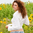Beautiful young girl in summer sunflowers — Stock Photo