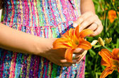 Young pregnant woman and flower daylily — Stock Photo