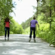 Stock Video: Lovers ride on Rollerblade in park
