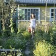 Young woman with a bucket is in the garden — Vídeo Stock