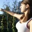 Young woman watering garden and squinting against the sun — Stock Video