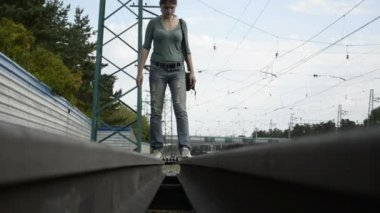 Young woman walking on the rail siding — Стоковое видео