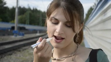 Young woman paints her lips on the railway — Stock Video