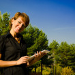 Стоковое фото: Young woman running on a Tablet PC in the autumn park