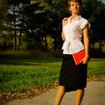 Бизнес-леди, писать в записной книжке в Осенний парк на треке — Стоковое фото