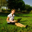 Businesswoman uses a laptop in autumn park sitting on the grass — Stock fotografie