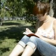 Young womreading book in park sitting on grass — Stok Video #14035724